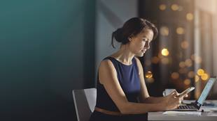 woman with phone and laptop at desk