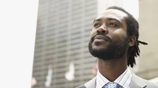 Young black male law student looking up optimistically in an urban cityscape