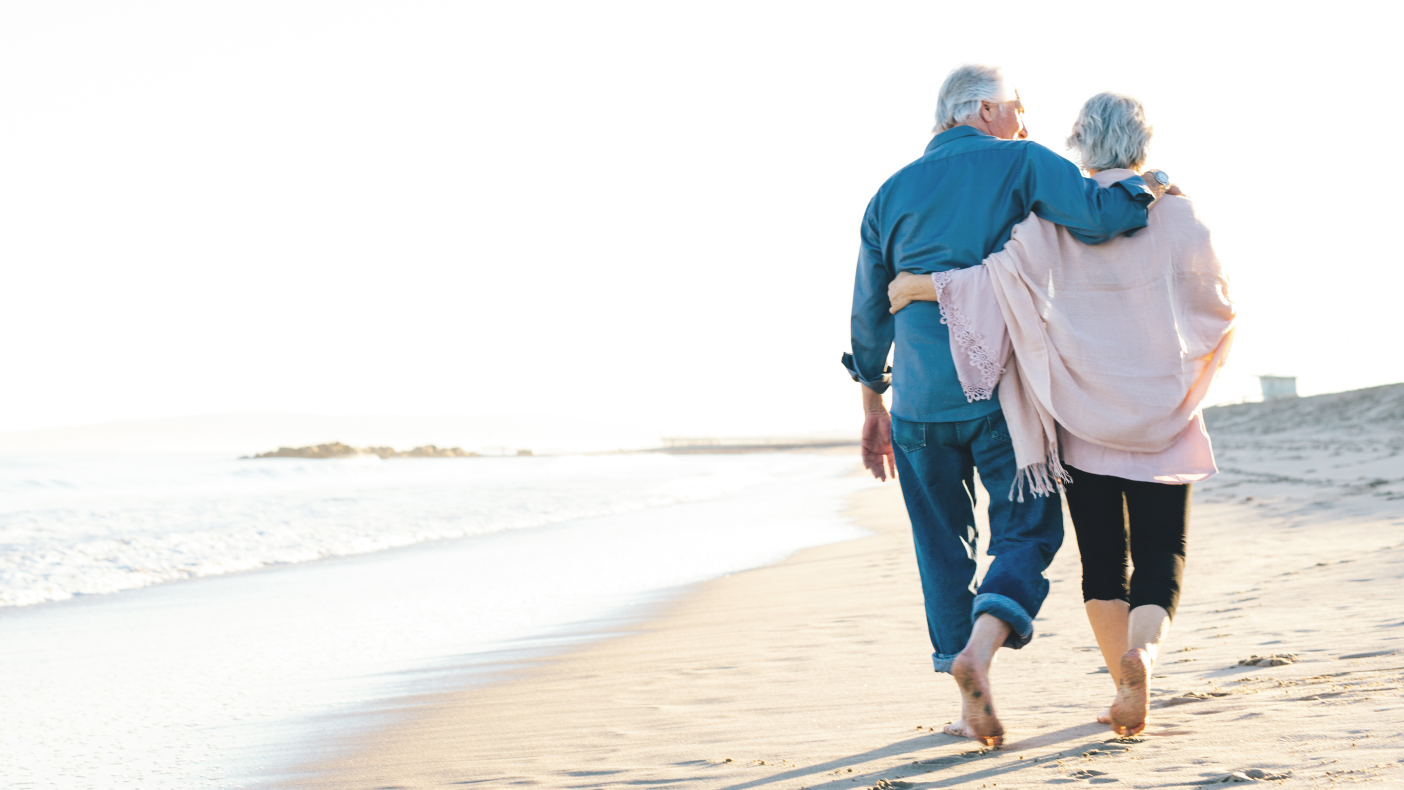 two older people walking on beach