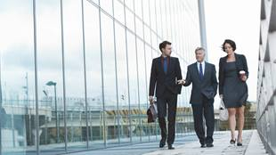 three business people walking over a glass footbridge