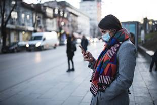 Woman outside with face back using her smartphone