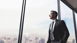 man looking out window in tall building