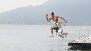 father and son jumping off dock
